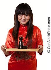 Serving saki - Attractive asian woman wearing orange satin...