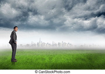 Composite image of serious businessman with hands on hips -...