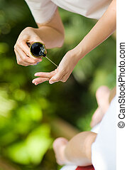 Massage Oil - A massage therapist pours oil into her hands