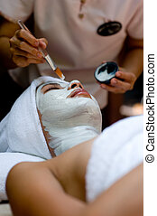 Spa Treatment - A young woman has a facial treatment at a...