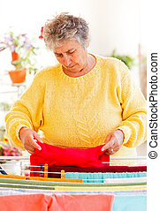 Housework - Elderly woman put the wet clothes on the dryer