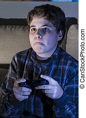 Leisure. boy with joystick playing computer game at home. -...