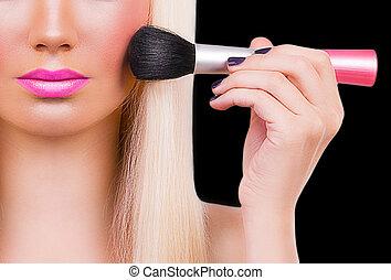 Beautiful girl with makeup brush