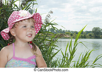 Summer on the lake near the reeds  little girl in panama hat.