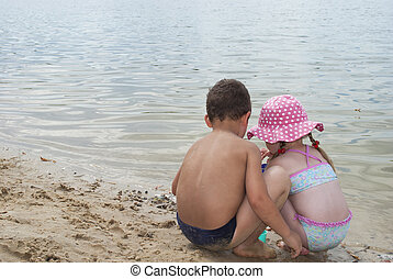 Young children playing on the beach near the lake.