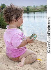 n the summer, on the beach near the lake in the sand little girl playing with toys