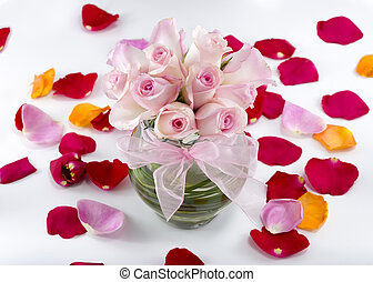 Collection of multicolored rose petals arranged with a vase...