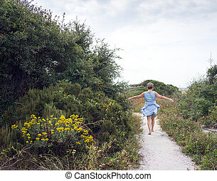 Mature Woman Walking Path to the Beach - Senior woman...