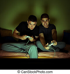 Friends playing video games. Selected focus on face of man...