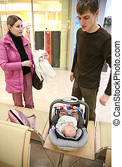 parents with baby in shop