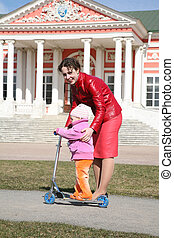 mother with baby on scooter in kuskovo moscow