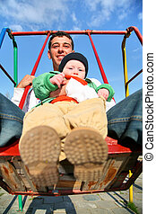 father with baby on seesaw