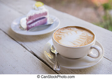 Cup of latte coffee and cake