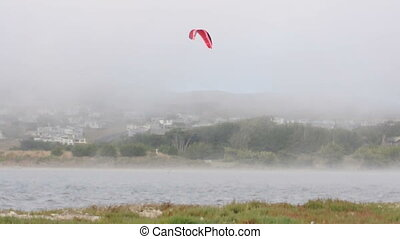 A parachute  surfer glides across the water in Bodega Bay