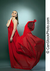 Graceful naked girl posing in red flying cloth, on gray...