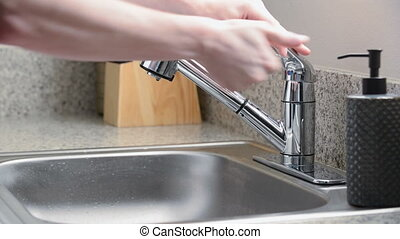 Man leaves kitchen sink faucet running after washing hands