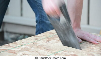 Angled view of man sawing wood plank