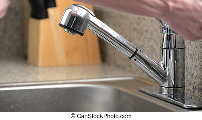 Man washes hands in kitchen sink