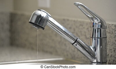 Close up of man turning off dripping kitchen sink faucet