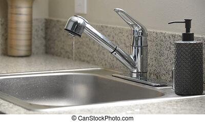 Man turns off dripping kitchen sink