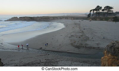 Visitors walk along the beach at sunset, time lapse