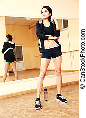 Young fit woman standing at gym