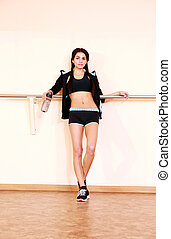 Young pensive fit woman standing at gym