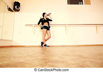 Full-length portrait of a young fit woman drinking water at gym