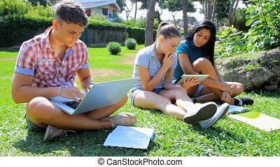 Studying with technology is fun - Three students studying...