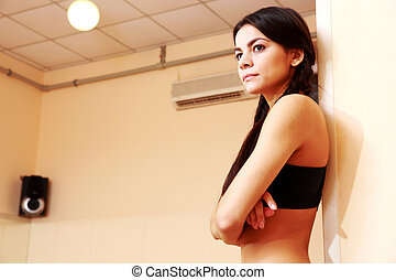 Young pensive fit woman at gym