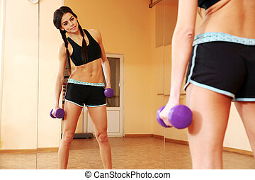 Young fit woman doing exercises with dumbells and looking at...