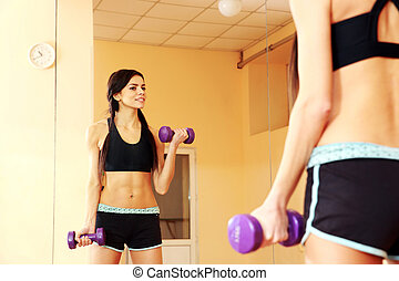 Young smiling fit woman doing exercises with dumbells and...