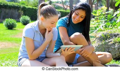 Two girls having fun with ipad tab - wo beautiful girls...