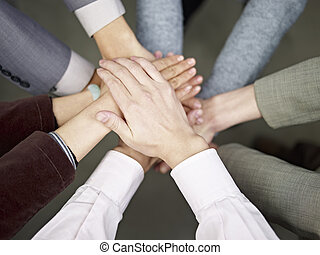 business team putting hands together - team of...