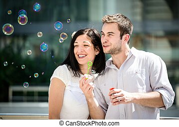 Fun with bubble blower - Young couple play together with...