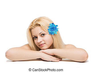 Young beautiful blonde girl with blue flower in hair