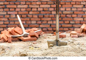 Shovel and pickaxe on a construction site, brick wall...