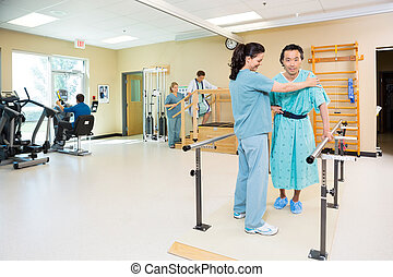 Therapists Assisting Patients In Hospital Gym - Physical...