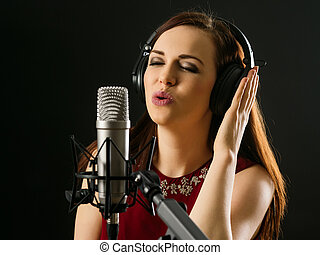 Singing into a studio microphone - Photo of a beautiful...