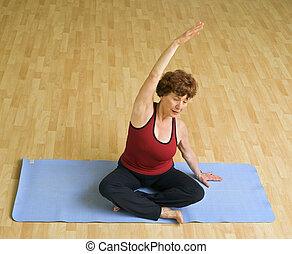 senior woman exercising yoga - senior woman doing yoga in a...