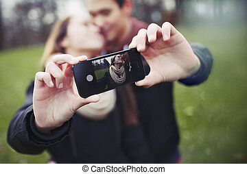 Romantic teenage couple taking self portrait with cell phone...