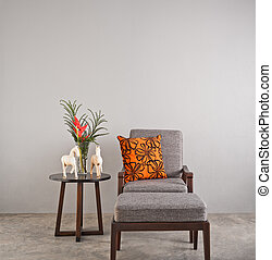 Grey upholstered chair with footstool and orange pillow
