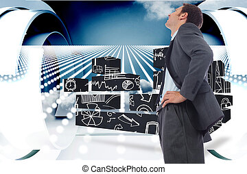 Cheerful businessman standing with hands on hips against abstract design in blue and white