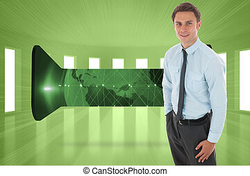 Happy businessman standing with hand in pocket against bright green room with windows