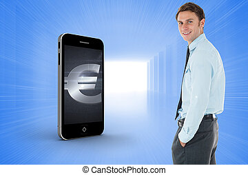 Happy businessman standing with hand in pocket against bright blue room