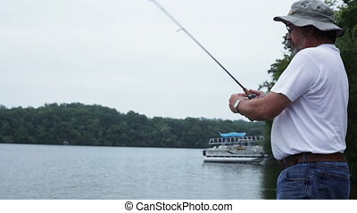 Fishing off dock - Mid-aged man casting off a dock and...