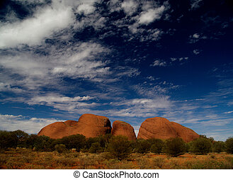 Kata Tjuta in sun, red, with blue cloudy sky