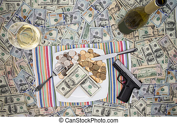 Handgun and champagne on 100 dollar bills - Overhead view of...