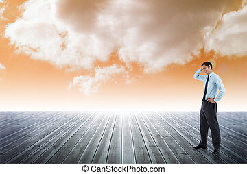 Composite image of thoughtful businessman with hand on head