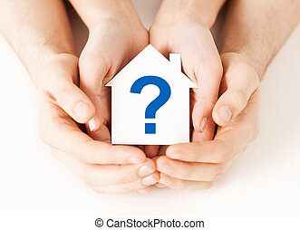 hands holding house with question mark - real estate and...